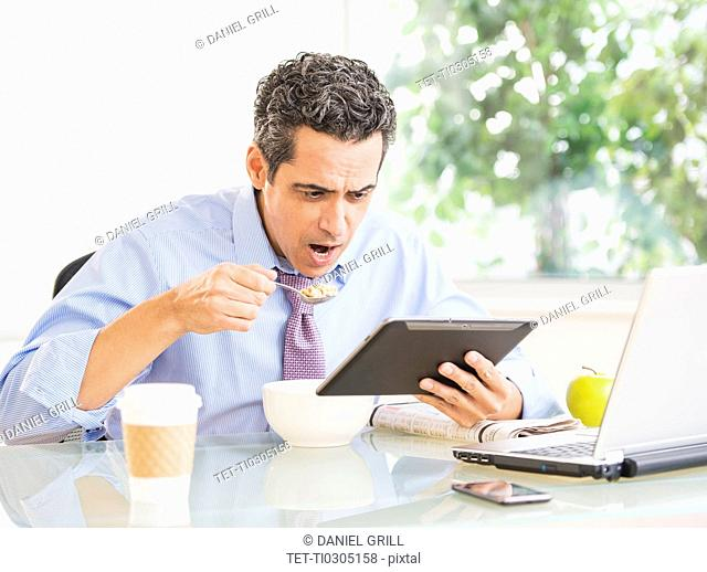 Portrait of man eating and using digital tablet