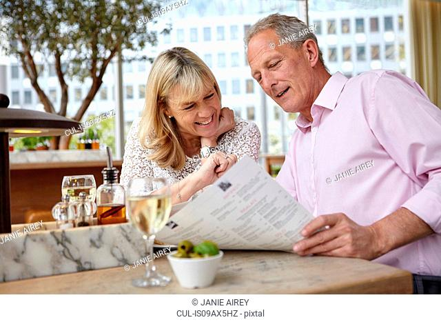 Mature dating couple reading menu at restaurant table
