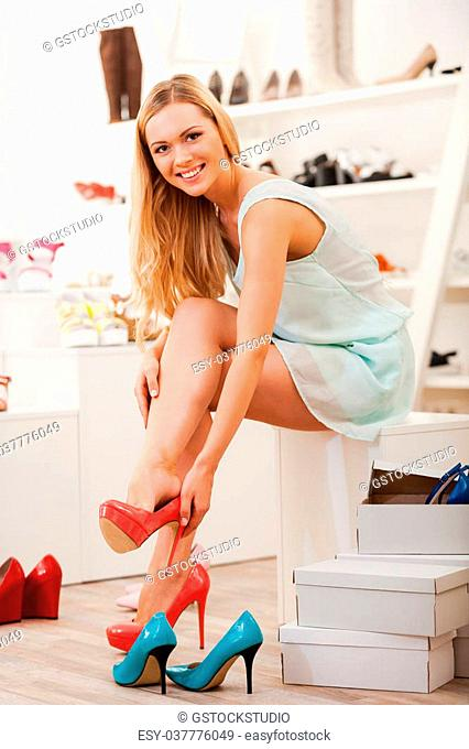 Time for new shoes. Smiling young woman trying on different shoes and looking at camera while sitting in shoe store