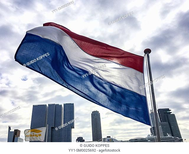 Rotterdam, Netherlands. Dutch national flag, tricoleur, waving in the wind, on the stern of a passenger ship crossing the Nieuwe Maas River inside port of...