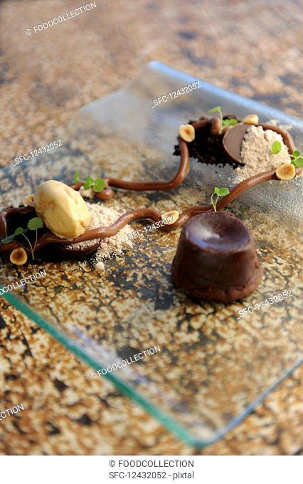 A deconstructed brownie dessert on a glass plate
