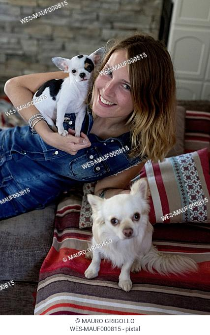 Smiling woman with her dogs on the couch at home