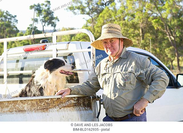 Caucasian farmer with dog in pick up truck