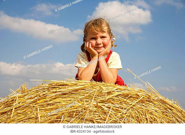 Little girl lying on a straw bale under a cloudy blue sky, Germany