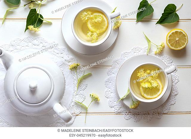 Two cups of herbal tea with linden flowers and lemon, top view