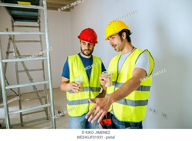 Two workers talking at work while drinking coffee