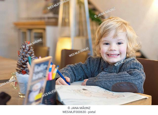 Smiling blond boy in a cafe, portrait