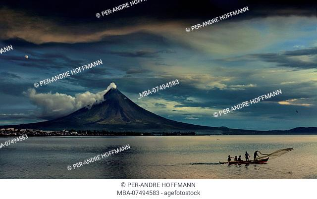fishermen on outrigger in front of steaming Mayon Volcano, Legazpi City, Luzon Island, Philippines, Asia