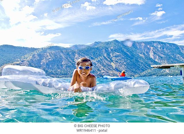 Boy swims with a toy floatie in a lake
