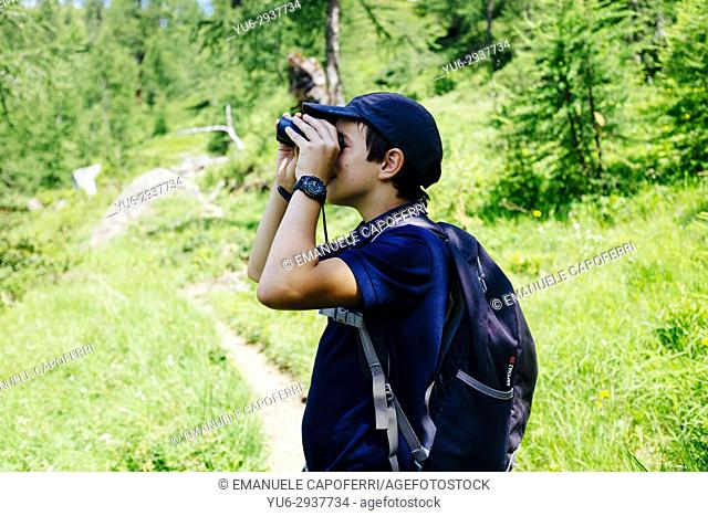 boy looks with binoculars in the mountains. Alpe Devero, Piemonte, Italy