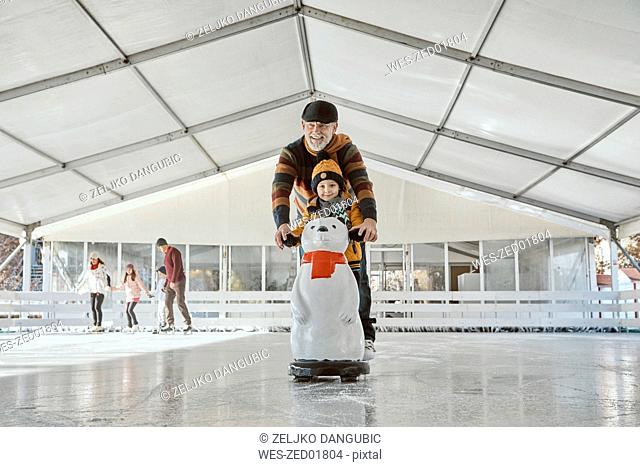 Grandfather and grandson on the ice rink, ice skating, using ice bear figure as prop