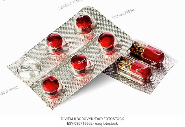 Pile of pills and capsules in package isolated on white background