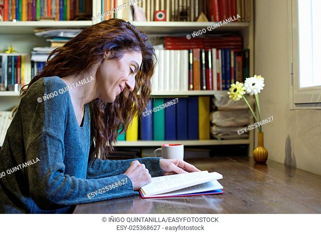 smiling happy brunette woman with green sweater reading red book on wooden table with cup of coffee, library behind