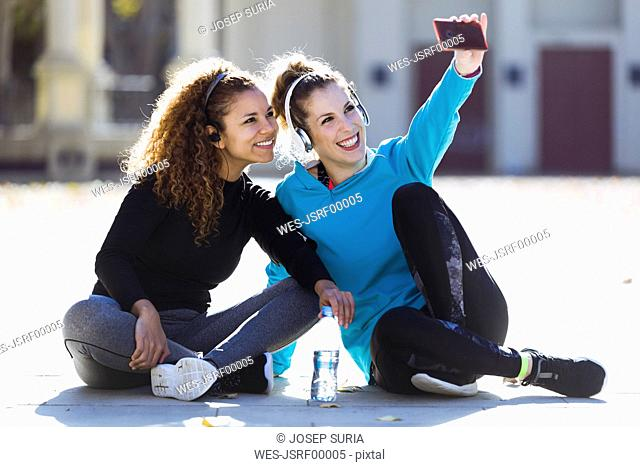 Two smiling sportive young women having a break taking a selfie
