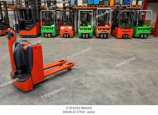 Mechanical dolly and forklift machinery in warehouse