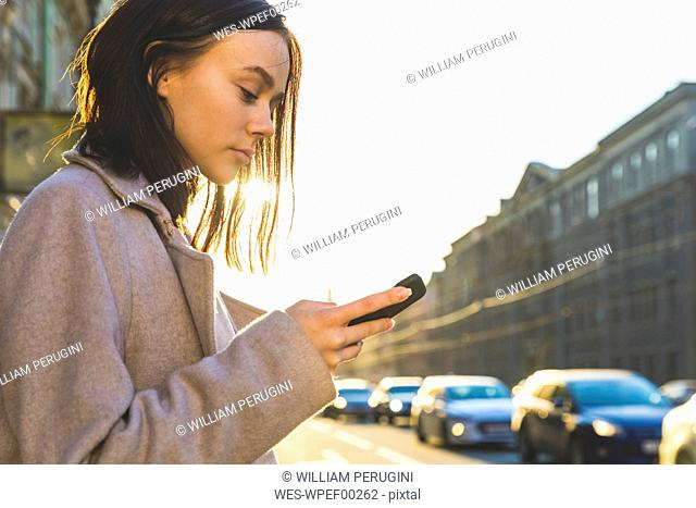 Russia, St. Petersburg, young woman using smartphone in the city