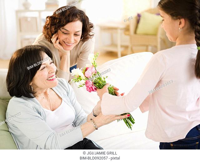 Granddaughter giving grandmother bouquet of flowers
