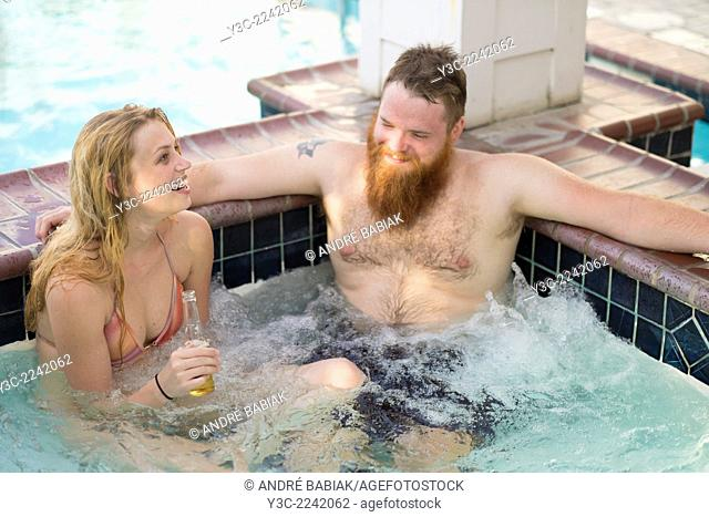 Jacuzzi in wellness area of hotel with young adults drinking beer and laughing