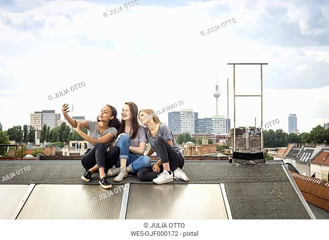 Germany, Berlin, three friends sitting side by side on roof top taking selfie with smartphone
