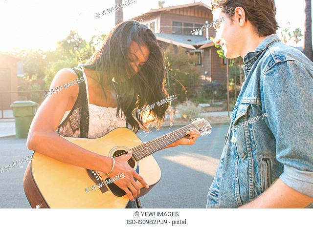 Young couple outdoors, young woman playing guitar