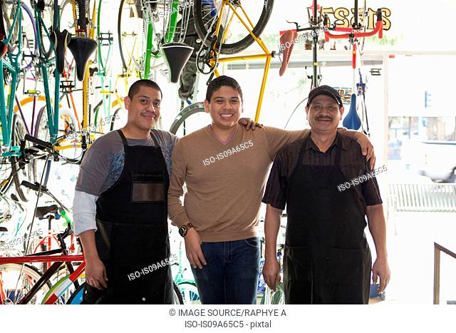 Mechanics smiling in bicycle shop