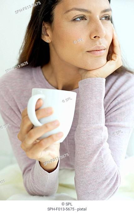MODEL RELEASED. Young woman holding mug with hot drink, looking away