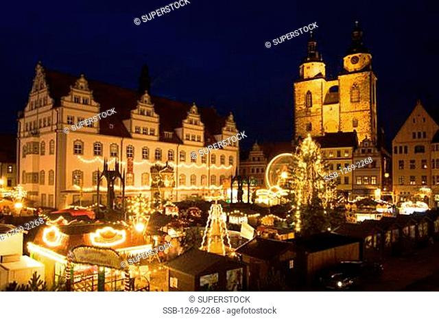 Buildings in a city lit up at night, Christmas Market, Wittenberg, Germany