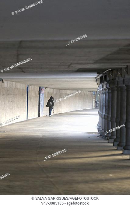 A woman walks under the seaside promenade of La Concha Beach in San Sebastan, Donosti, Basque Country