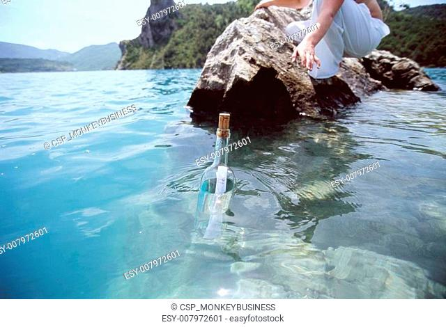 Woman reaching for a message in a bottle floating in sea