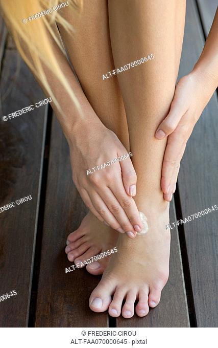 Woman moisturizing feet, cropped