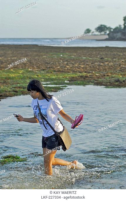 Balinese woman wading through the water at low tide, Pura Geger, Southern Bali, Indonesia, Asia