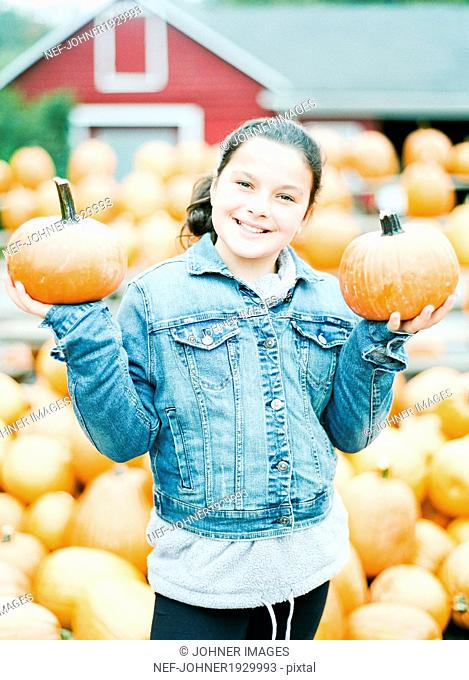Smiling girl with pumpkins, New Jersey, USA