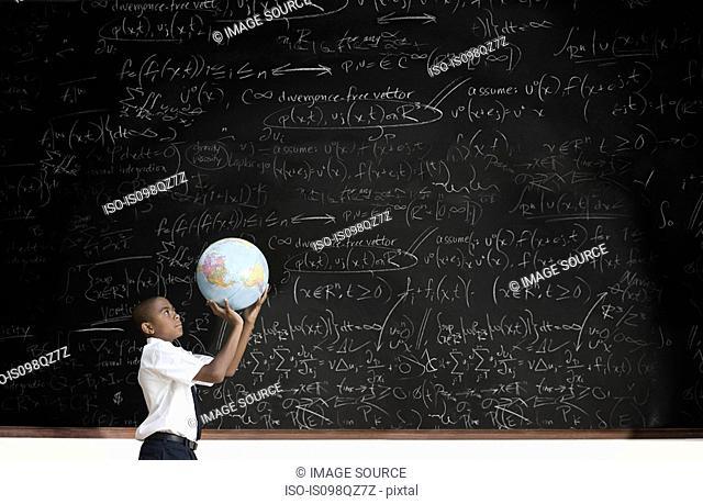 Boy with globe in front of blackboard
