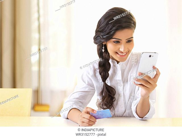 Young woman using phone and holding a credit card