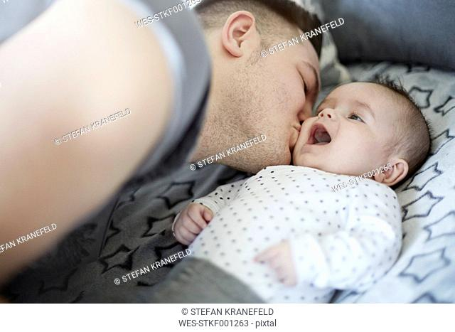 Young father kissing baby