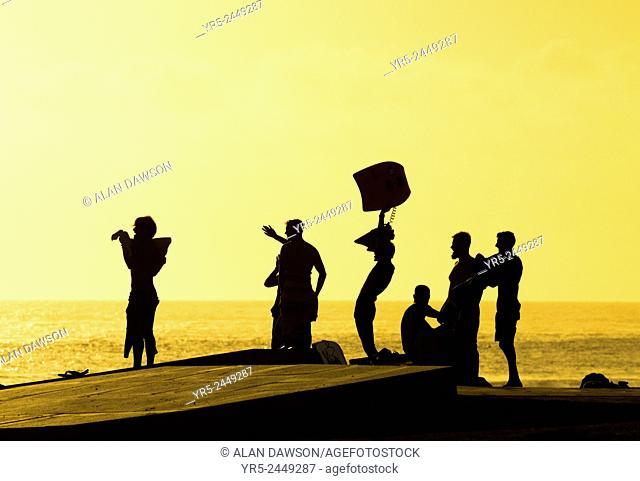 Surfers at sunset at El Confital beach, Las Palmas, Gran Canaria, Canary Islands, Spain
