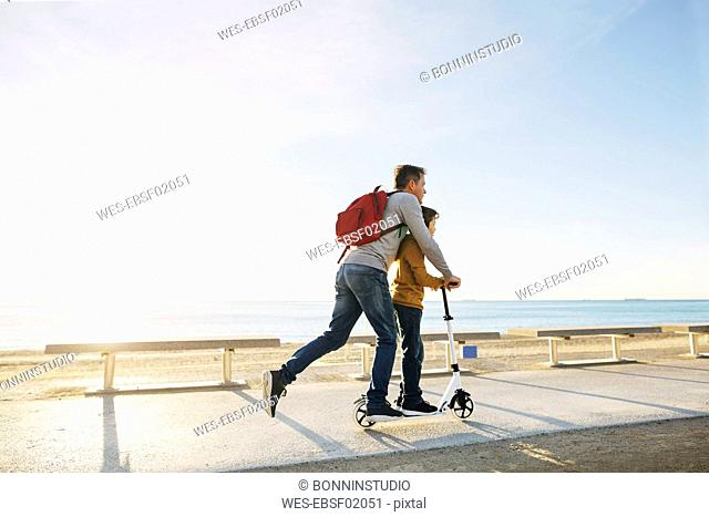 Father and son riding scooter on beach promenade at sunset
