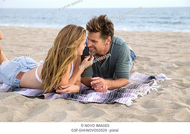 Smiling Mid-Adult Couple Looking at Each Other While Laying on Blanket at Beach