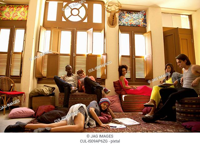 Students chilling out and studying in living room