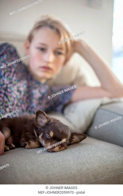 Teenage girl lying on sofa and napping with puppy