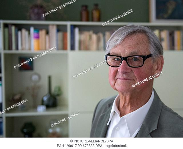 10 May 2019, Saxony, Leipzig: The well-known furniture designer Rudolf Horn stands in his Leipzig apartment in his study before furniture designs from the 1960s...
