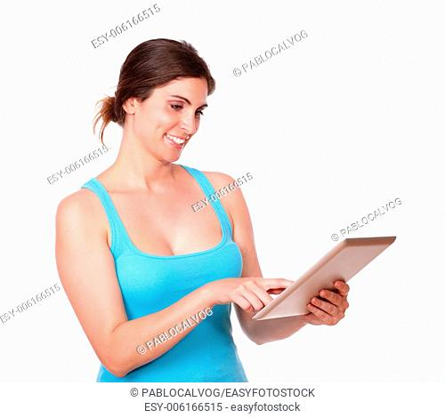 Portrait of a charming young woman using tablet pc while standing on isolated background