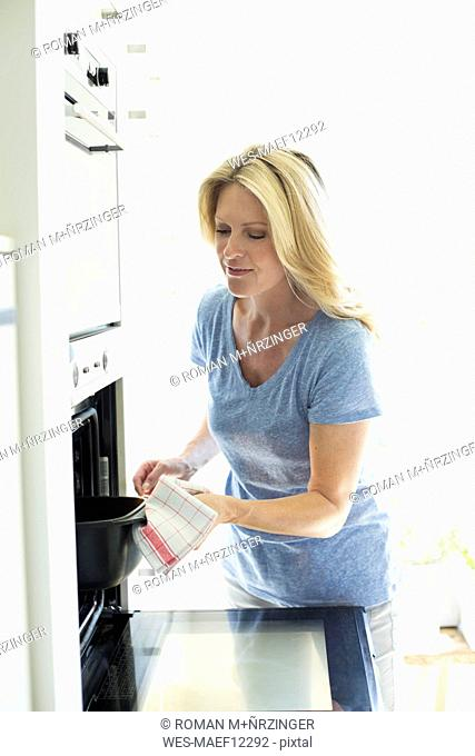 Woman in kitchen taking casserole dish out of oven