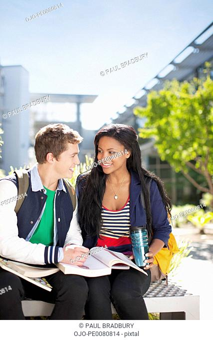 Students reading book together outdoors