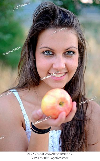 Young cute woman holding a red apple