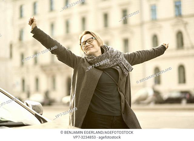 blithe woman dancing at street in city Munich, Germany