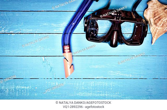 scuba mask and snorkel on a blue wooden background, empty space