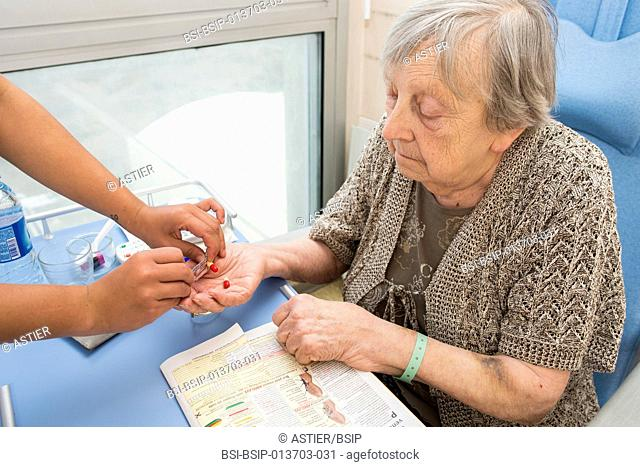 Reportage in the Follow-up Care and Rehabilitation service of Saint-Philibert hospital in Lille, France. A nurse gives a patient medicine in her hospital room