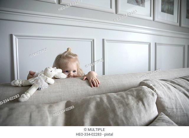 Girl with stuffed animal hiding behind living room sofa