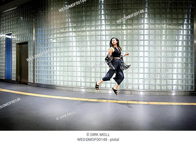 Fashionable young woman jumping in the air